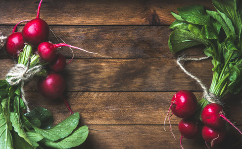 Fresh radish bunches over rustic wooden background  copy space