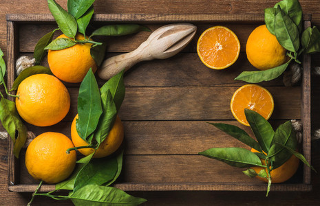 Fresh oranges with leaves in dark wooden tray over rustic background  copy space