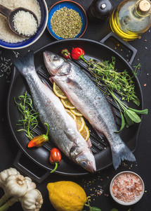 Ingredients for cookig healthy fish dinner Raw uncooked seabass with rice lemon olive oil herbs and spices on black grilling iron pan over dark background