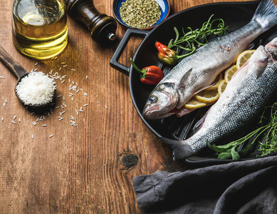 Ingredients for cookig healthy fish dinner Raw uncooked seabass  with rice olive oil lemon slices herbs and spices on black grilling iron pan over rustic wooden background copy space