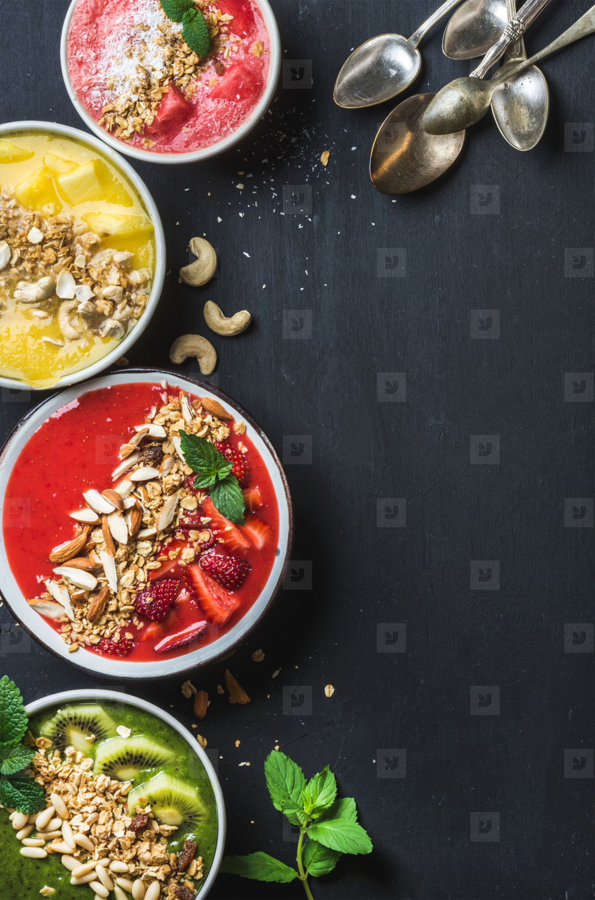 Healthy summer breakfast concept  Colorful fruit smoothie bowls with nuts  oat granola and mint leaves  five silver spoons on black background  Yellow  pink  red  green  Top view  copy space