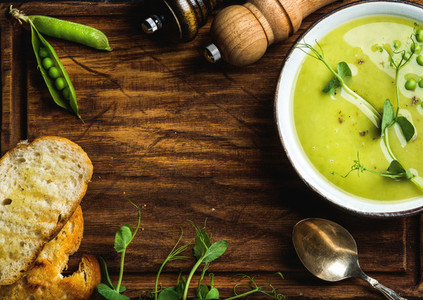 Green pea cream soup on wooden background  copy space