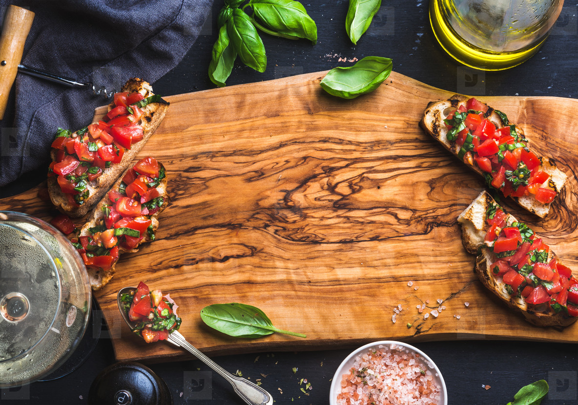 Tomato and basil bruschetta with glass of white wine on olive wooden board over black background