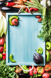 Fresh raw vegetable ingredients for healthy cooking or salad making on wooden background and blue  tray in center  top view  copy space