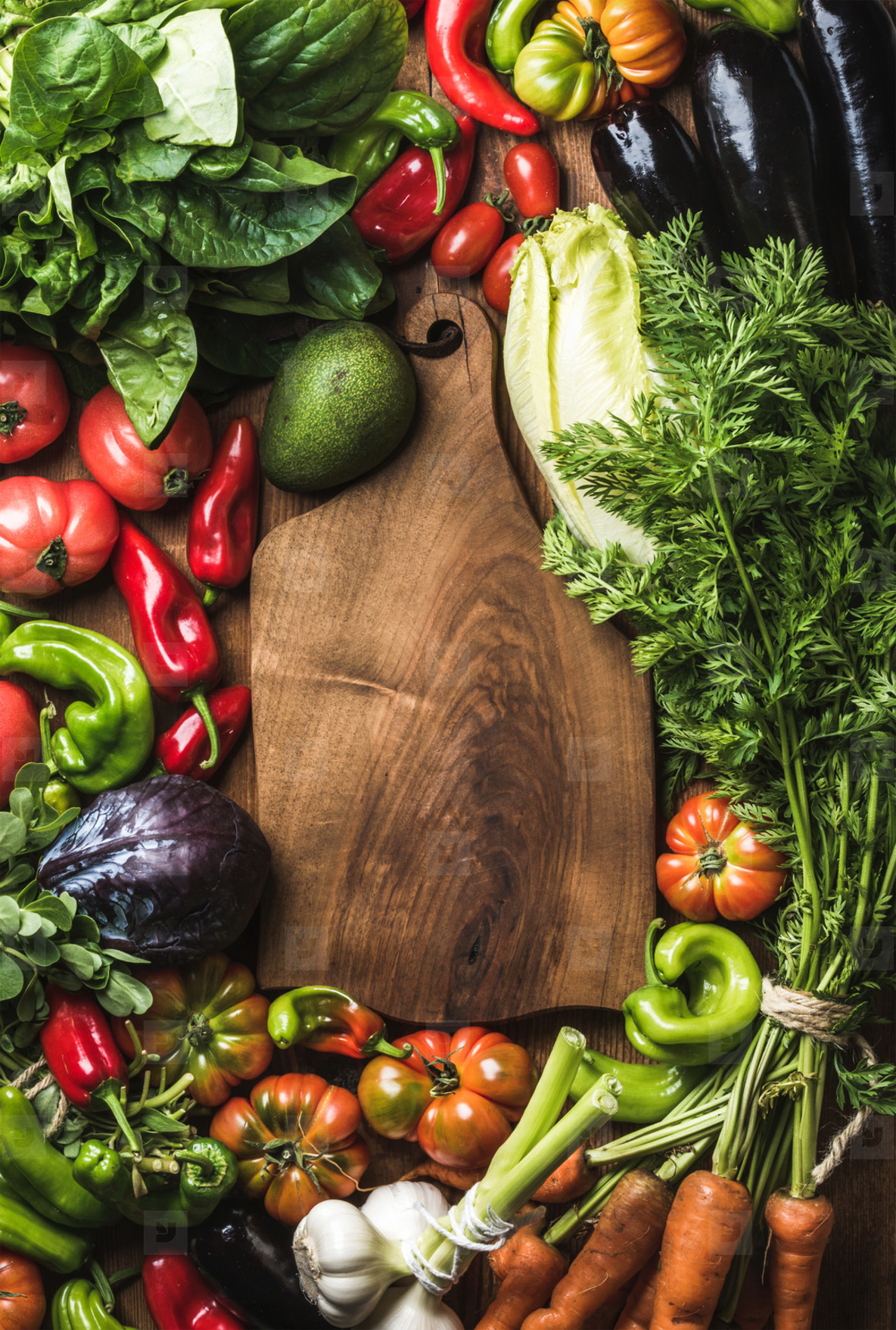 Fresh raw vegetable ingredients for healthy cooking or salad making with rustic wood board in center  top view  copy space  vertical composition