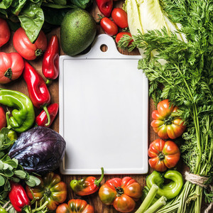 Fresh raw vegetable ingredients for healthy cooking or salad making with white ceramic board in center over wooden background top view copy space vertical composition
