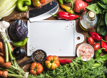 Fresh raw vegetable ingredients for healthy cooking or salad making with white ceramic board in center  top view  copy space