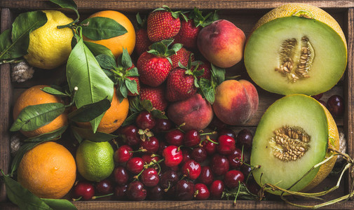 Healthy summer fruit variety  Melon  sweet cherries  peach  strawberry  orange and lemon on wooden tray background
