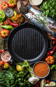 Raw uncooked seabass fish vegetables grains herbs spices and olive oil on chopping board iron grilling pan in center with copy space top view