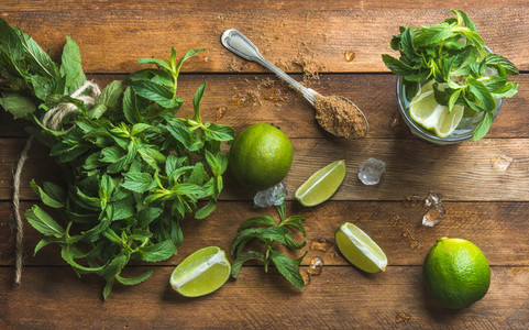 Ingredients for making mojito summer cocktail Fresh mint bunch and leaves limes spoon of brown sugar ice over rustic wooden background top view