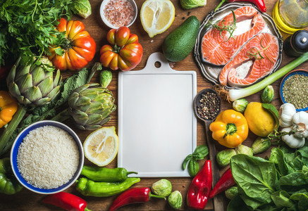 Raw uncooked salmon fish in small metal plate with vegetables  rice  herbs  spices  olive oil on rustic wooden background  white ceramic board in center  copy space  top view