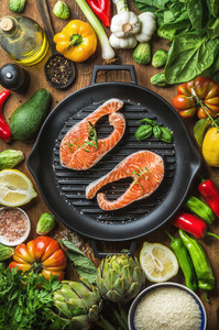 Dinner cooking ingredients Raw uncooked salmon with vegetables rice herbs lemon artichokes spices in iron grilling pan over wooden background top view