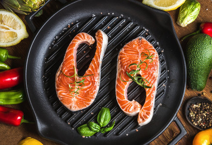 Dinner cooking ingredients Two pieces of raw uncooked salmon with vegetables herbs lemon avocado artichokes spices in iron grilling pan over wooden background
