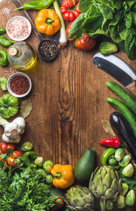 Fresh raw vegetable ingredients for healthy cooking or salad making on wooden background  copy space in center  top view  Diet   vegetarian food concept