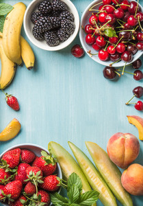 Healthy summer fruit variety  Sweet cherries  strawberries  blackberries  peaches  bananas  melon slices and mint leaves on blue backdrop with copy space in center  top view