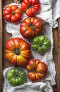 Colorful Heirloom tomatoes on white textile in rustic wooden tray  top view