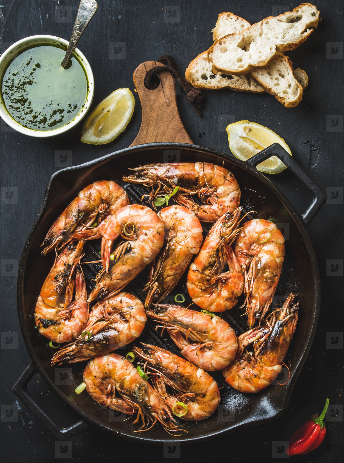 Roasted tiger prawns in iron grilling pan on wooden board