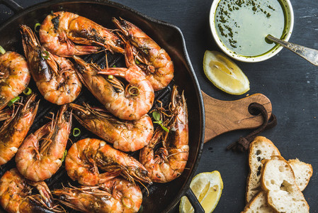 Roasted tiger prawns in iron grilling pan with fresh leek lemon slices bread and pesto sauce over black background