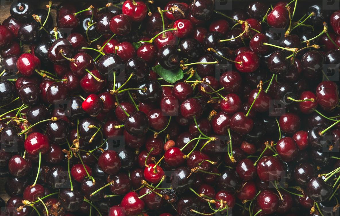 Background of dark red sweet cherries over wooden backdrop