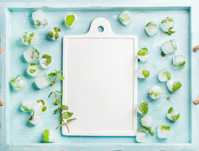 Ice cubes with frozen mint leaves inside in blue Turquoise tray and white ceramic board in center  copy space
