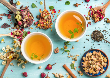 Two cups of healthy herbal tea with mint  cinnamon  dried rose and camomile flowers in spoons over blue background