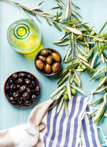 Two bowls with pickled green and black olives  olive tree sprigs  fresh homemade oil over blue Turquoise background
