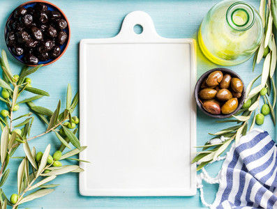 Two bowls with pickled green and black olives  olive tree sprigs  oil in glass bottle  white ceramic board in center over blue background  copy space
