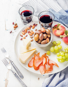 Wine snack set  Cheese  chicken carpaccio  mediterranean olives  fruits  nuts and two glasses of red on ceramic plate over white wooden background
