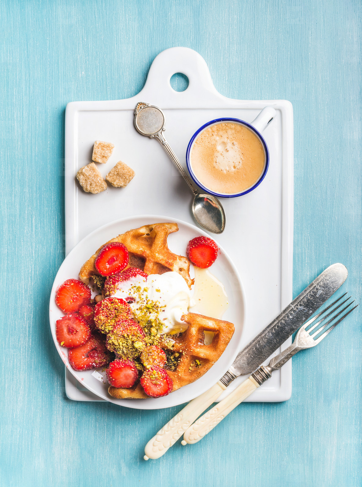 Breakfast set  Warm homemade belgium waffles with whipped cream  strawberry  maple syrup  crushed pistachios  cup of espresso and brown sugar on white ceramic board over blue painted wooden background