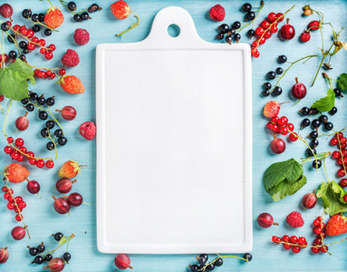 Healthy summer garden berry variety Black and red currant gooseberry rasberry strawberry mint leaves on blue painted backdrop with white ceramic board in center copy space