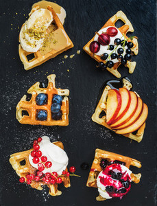 Warm belgian homemade waffles with fresh garden berries fruit and ice cream on dark slate stone background