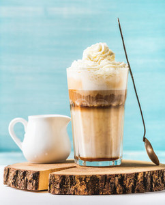 Latte macchiato with whipped cream  serving silver spoon and white pitcher on wooden round board over blue painted wall background