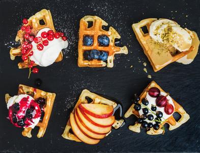 Warm belgian homemade waffles with fresh garden berries  fruit and ice cream on dark slate stone background