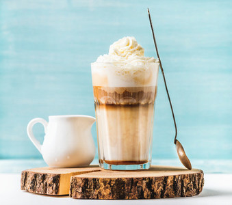 Latte macchiato with whipped cream serving silver spoon and pitcher on wooden round board over blue painted wall background