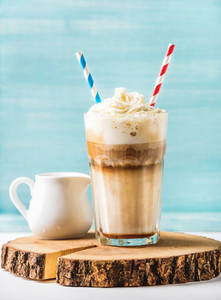 Latte macchiato with whipped cream in tall glass and pitcher on round wooden board over blue painted wall background