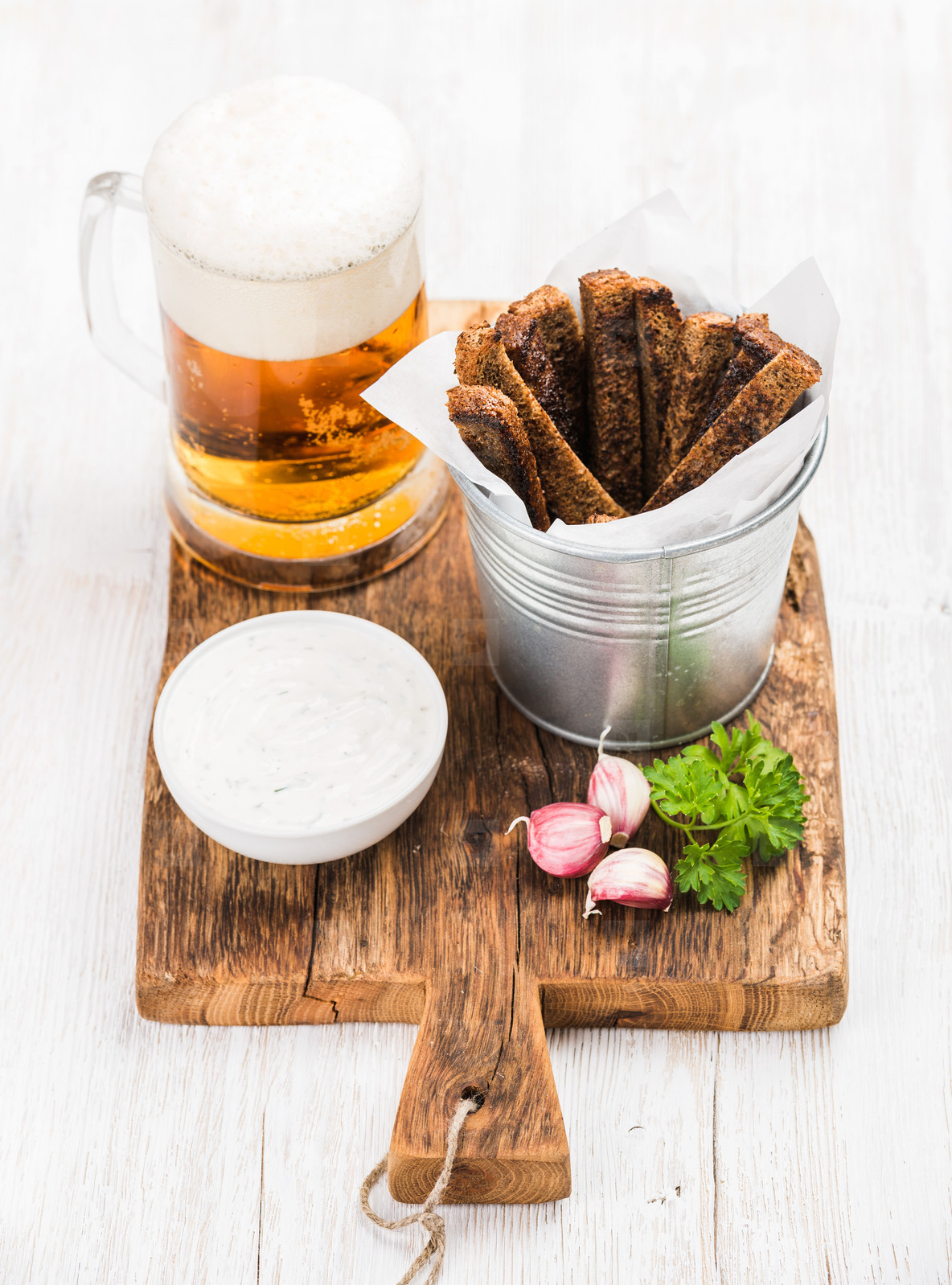 Beer snack set  Pint of pilsener in mug  open glass bottle  rye bread croutons with garlic cream cheese sauce and fresh parsley on rustic wooden board over white painted old background