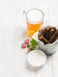 Beer snack set Pint of pilsener in tall mug and rye bread croutons with garlic cream cheese sauce over white painted old wooden background