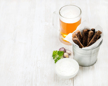 Beer snack set  Pint of pilsener in glass mug and rye bread croutons with garlic cream cheese sauce over white painted old wooden background
