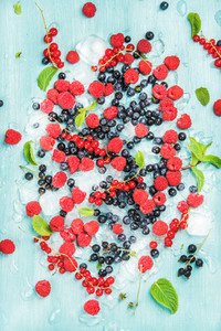 Fresh summer garden berry variety  Rasberry  black and red currant  bilberrry  mint on crushed ice over blue background
