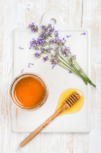 Lavender honey in glass jar with flowers on white background