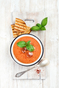 Cold gazpacho soup with ice and basil over white background