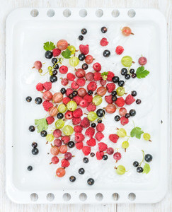 Fresh summer garden berries variety on white baking tray over light wooden backdrop