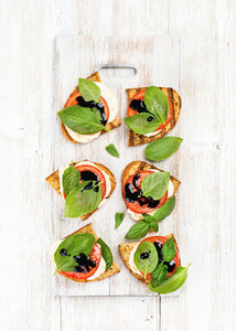 Caprese sandwiches with tomato  mozzarella cheese  basil and balsamic glaze on white painted wooden background