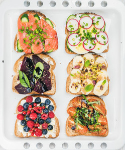 Sweet and savory breakfast toasts assortment  Sandwiches with fruit  vegetables  eggs  smoked salmon on white baking tray background