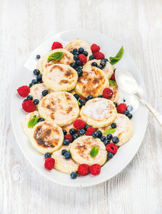 Syrniki or cottage cheese pancakes with fresh forest berries and sour cream sauce in serving dish over white wooden background