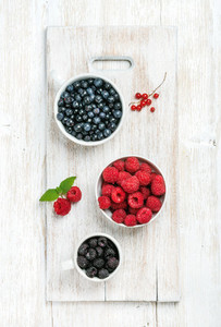 Summer garden berries in bowls on white painted wooden background