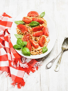Spaghetti with roasted tomatoes and fresh basil over white background