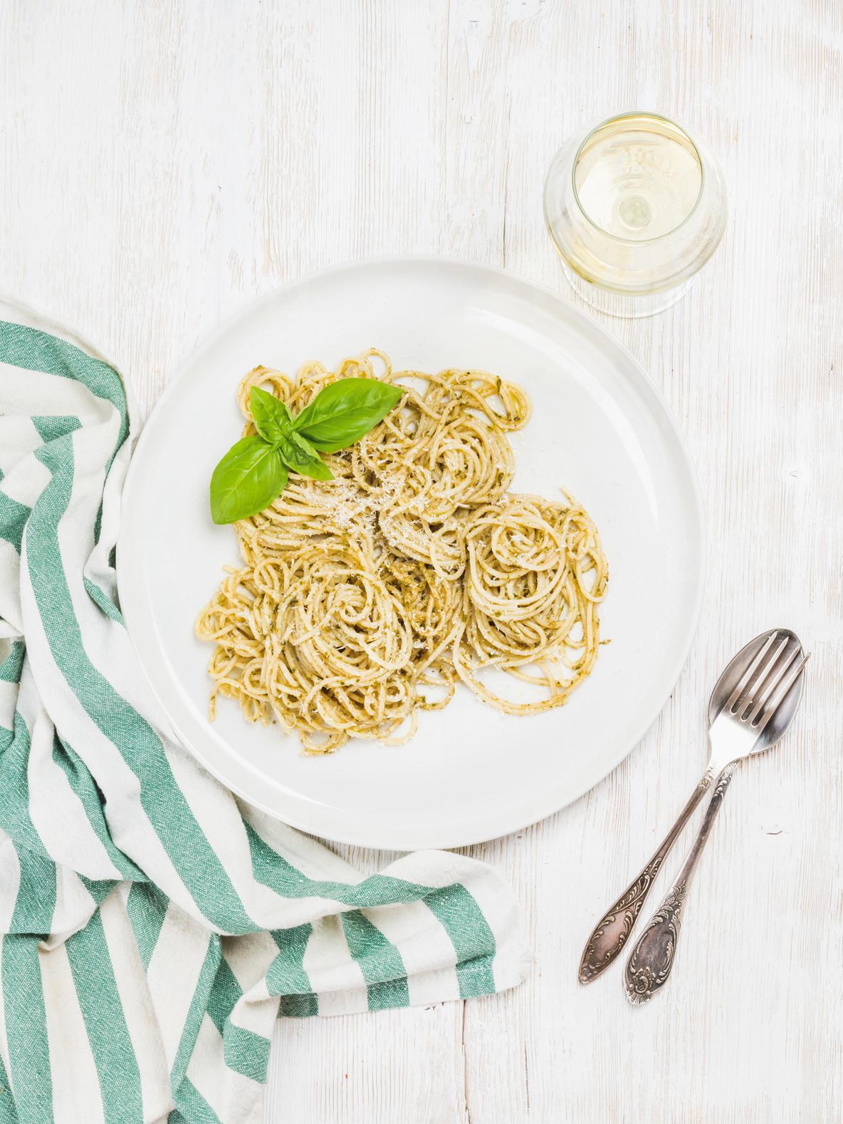 Pasta spaghetti with pesto sauce  fresh basil  glass of white
