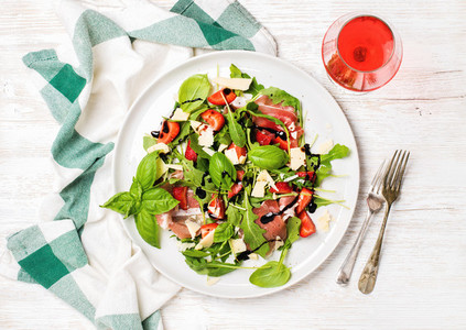 Summer arugula  prosciutto  strawberry salad with glass of rose wine