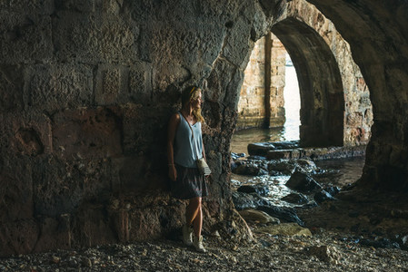 Young blond tourist woman stading in ancient stone shipyard and looking at the sea in the Old city  Alanya  Turkey